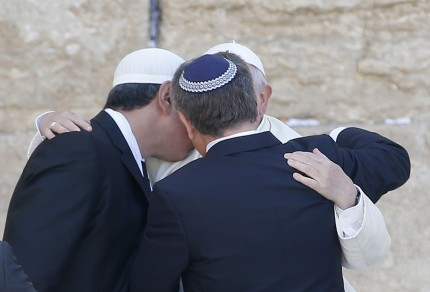 Pope Francis hugs two close Jewish and Muslim friends traveling with him at the Western Wall in Jerusalem's Old City on May 26, 2014. Pope Francis faces a diplomatic high-wire act as he visits sacred Muslim and Jewish sites in Jerusalem on the final day of his Middle East tour. AFP PHOTO/ THOMAS COEX / AFP / THOMAS COEX