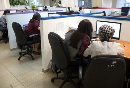 Ultra-Orthodox Jewish women work on computers at their desks in the Comax software company office in the central city of Holon near Tel Aviv on April 17, 2016.  The company in Holon near Tel Aviv employs 20 ultra-Orthodox women, one of several to do so as increasingly more female breadwinners from Israel's religious community join the secular work force. Graduates of programming schools in the overwhelmingly ultra-Orthodox community of Bnei Brak, about 10 kilometres (six miles) away, the Comax women produce most of the firm's computer programmes for large supermarkets in the vicinity.       / AFP PHOTO / MENAHEM KAHANA / TO GO WITH AFP STORY BY DELPHINE MATTHIEUSSENT